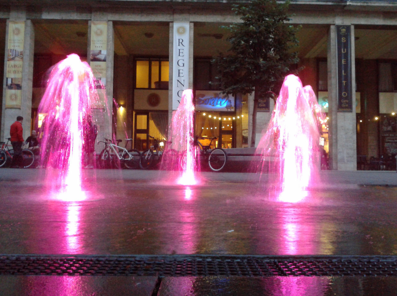 illuminated, night, architecture, motion, built structure, building exterior, long exposure, incidental people, architectural column, real people, city, pink color, blurred motion, men, outdoors, glowing, fountain, building, event, light, purple