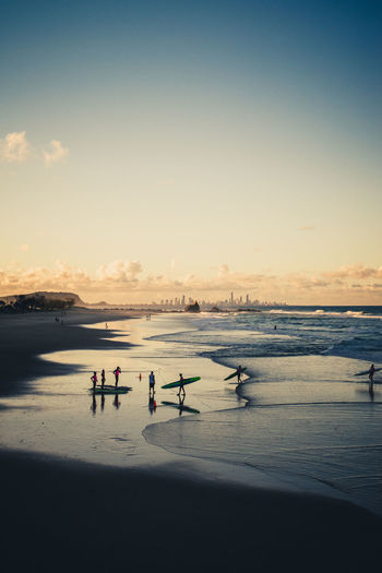 Surfers At Beach Against Sky During Sunset