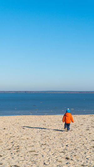 Rear view full length of boy walking at beach against clear blue sky