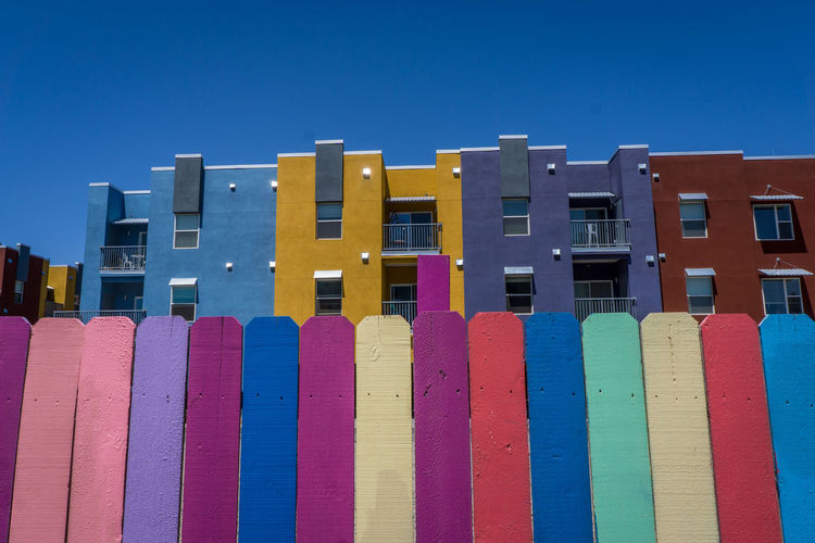 Low angle view of multi colored buildings against blue sky