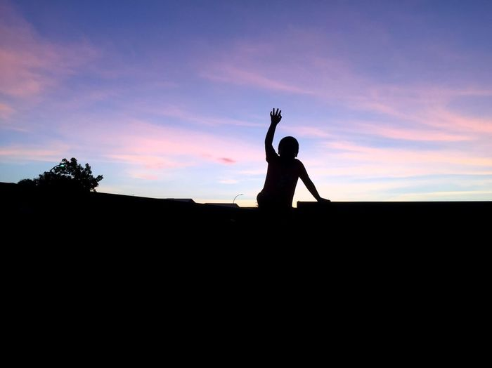 Silhouette boy on rooftop against sky during sunset