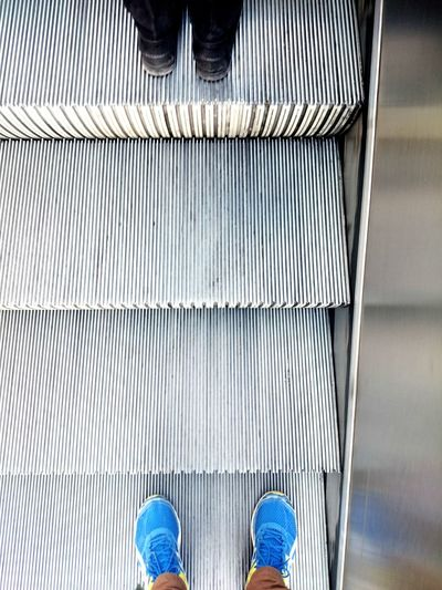 Low section of woman standing on escalator