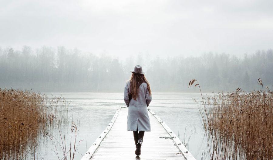 Rear view of woman walking on lake during winter