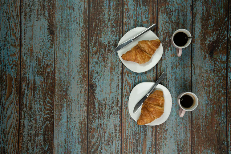 freshly baked croissants with coffee on a old vintage wooden background. with space next to it for text Food And Drink Table Wood - Material Directly Above Food Cup Freshness Coffee Coffee Cup Still Life Mug Coffee - Drink Indoors  No People Drink Refreshment Wellbeing Eating Utensil Meal Spoon Breakfast Snack Espresso Delicious Wooden Vintage Rustic Croissant French Baked Copy Space Close-up Pastry Textured  Card Concept Backgrounds Black Plate Gold Freshly Lunch Home Morning Croissants Sweet