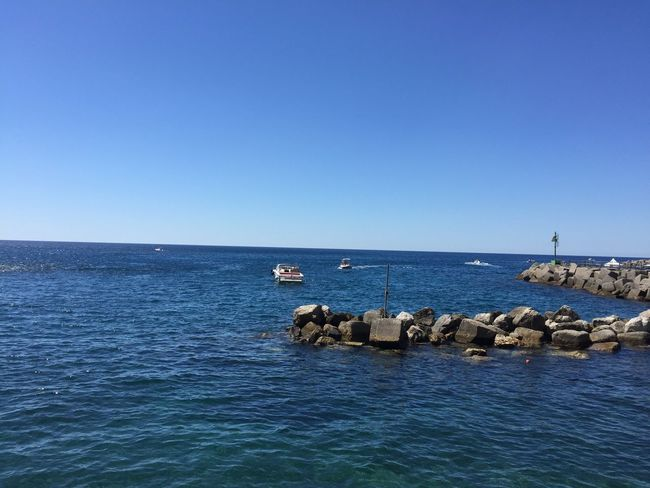 Deep blue sea and rocks at the shore under a deep blue sky meeting at horizon Beauty In Nature Blue Clear Sky Cool Colors Copy Space Day Horizon Over Water Nature No People Outdoors Scenics Sea Sea And Sky Seascape Sky Water