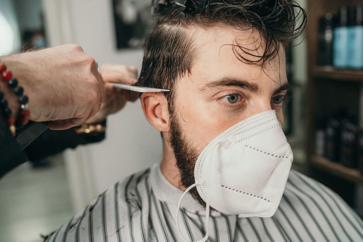 Male hairdresser haircutting hair to a young bearded man wearing a face mask due to coronavirus