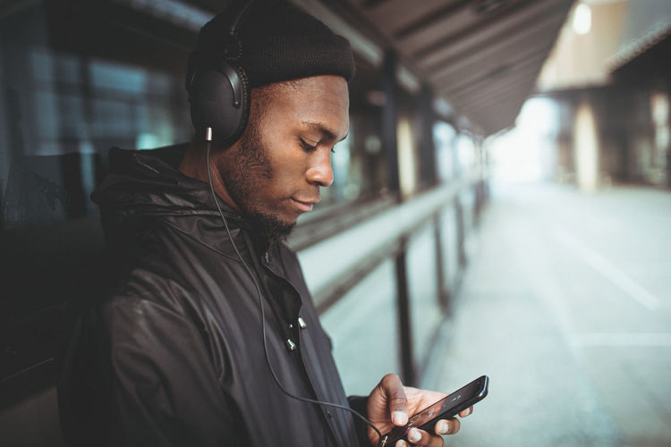 Man is listening to music with his smartphone Communication Connection Headphones Holding Jacket Lifestyles Listening Looking Looking Down Mobile Phone Music One Person Portability Portable Information Device Real People Side View Smart Phone Technology Text Messaging Urban Using Phone Wireless Technology Fresh On Market 2017