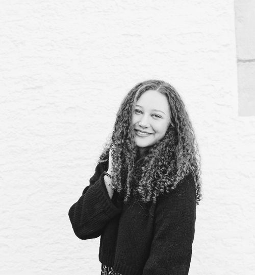Portrait of smiling young woman with curly hair standing against wall
