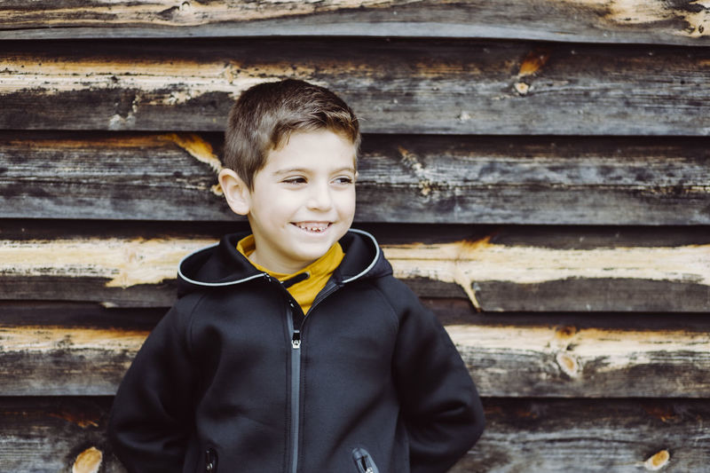 Smiling boy looking away against old wooden wall