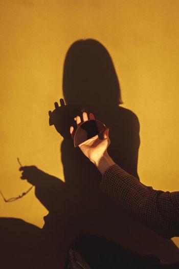 Portrait of silhouette man holding orange wall