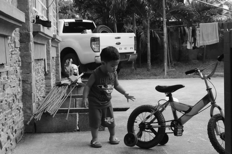 Full length of boy standing on bicycle