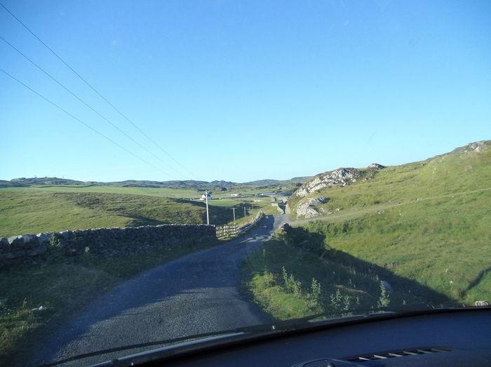 Road seen through car windshield against clear blue sky