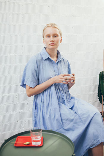 Portrait of young woman with coffee sitting against wall