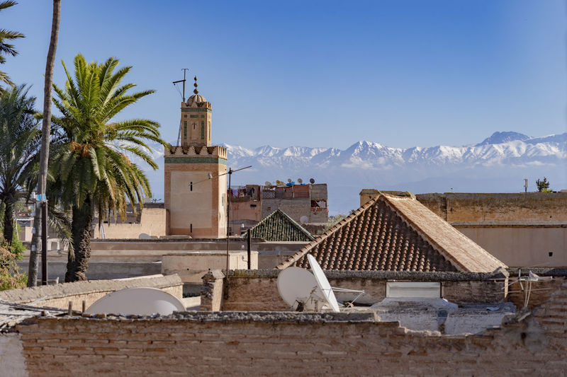 Architecture Building Exterior Mountain Sky Building Tree Day Plant Place Of Worship Religion Mountain Range Landscape Palm Tree Red Roofs Red Brick Red Brick Building Rooftop Rooftop View  Atlas Mountains Atlas Mountain Morocco Marrakech Marrakesh Mosque