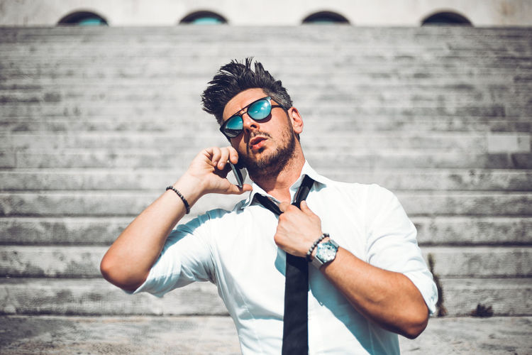 Midsection of man wearing sunglasses against wall