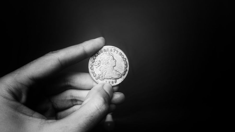 Close-up of hand holding coin against black background