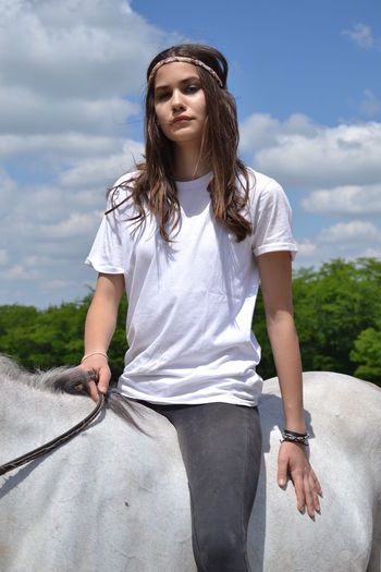 Horseriding Animal Themes Arabian Horse Beautiful Woman Casual Clothing Cloud - Sky Day Domestic Animals Front View Happiness Horse Indian Girl Leisure Activity Lifestyles Mammal Model Nature One Animal One Person Outdoors People Real People Sky Smiling Young Adult Young Women
