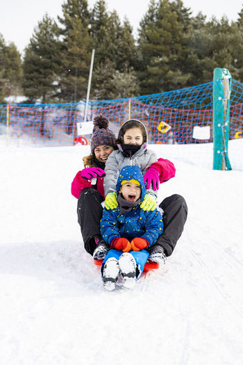 Portrait of family tobogganing on snow during winter