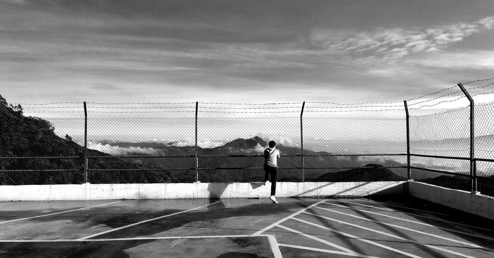 Rear view of mid adult man standing by fence against sky