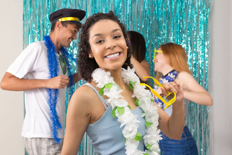 Portrait of smiling woman standing by friends during party