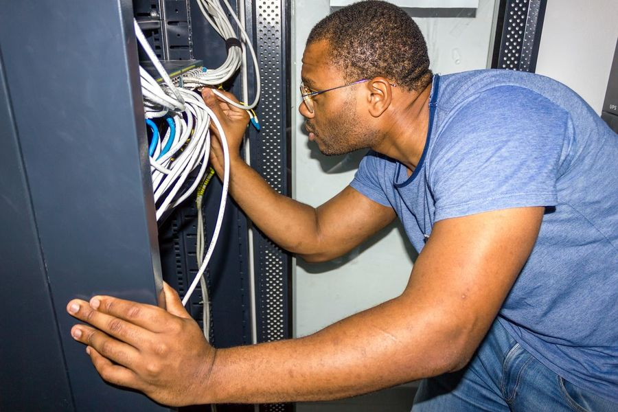 IT Guy working Angola IT IT Support Luanda Room Switch Working Adult Africa Cable Computer Cable Computer Network It Professional IT Support Men Network Server Networking Occupation One Person Professional Occupation Racks Server Room Technician Technology Telecommunication