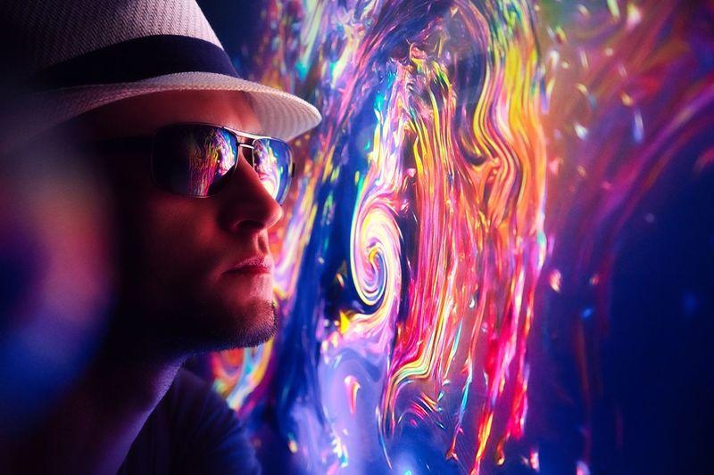 Man by illuminated multi colored pattern