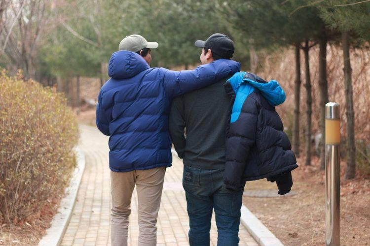 Best friends Warm Clothing Bonding Togetherness Men Friendship Full Length Standing Walking Rear View Blue Arm In Arm