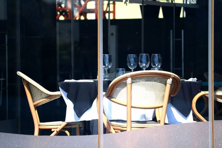 Outdoors Day No People Window Absence Empty Empty Places Empty Chair Furniture Transparent Glass - Material Glass Tablecloth Restaurant Restaurant Decor Seat Table Outdoor Furniture Close-up Reflection Table Setting Setting Chairs Arrangement Business Finance And Industry Chair Focus On Foreground Business Cafe Sunlight Architecture