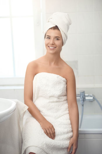 Happy young woman in her bathroom Beautiful Woman Beauty Indoors  One Person Young Adult Towel Wrapped In A Towel Adult Real People Woman Happy Enjoying Life Bathroom Domestic Life Home Shower Clean Freshness Smiling Looking At Camera Portrait Happiness Domestic Room Lifestyles Front View