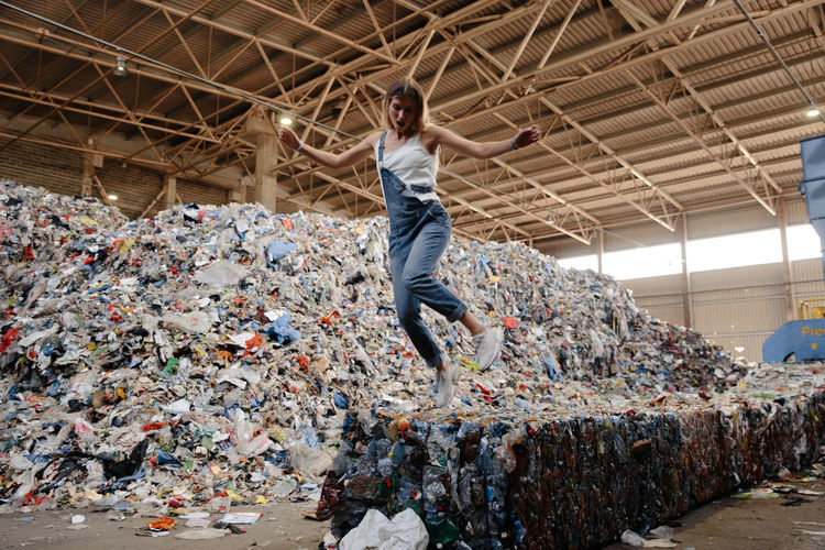 Full length of young woman jumping against garbage heap