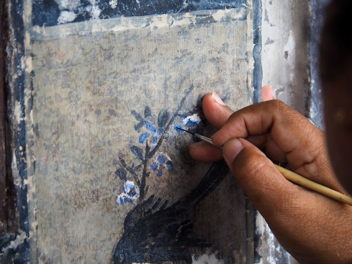 Close-up of hand painting on wall