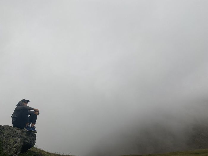 Man standing on foggy weather against sky