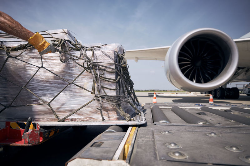 Hand of ground crew during unloading freight airplane. cargo containers against jet engine of plane.