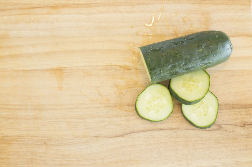 A knife and cucumbers on a wooden background. Horizontal image with space for copy. Close-up Copy Space Cucumber Cumcumber Day Food Food And Drink Freshness Fruit Healthy Eating High Angle View Indoors  No People SLICE Table Vegetable Wood - Material