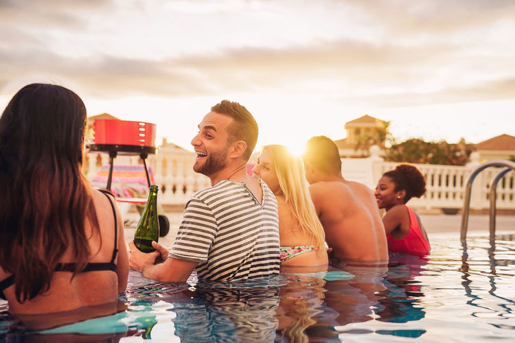 Friends In Swimming Pool During Sunset