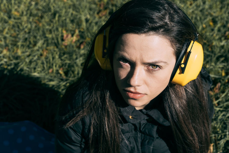 High Angle Portrait Of Young Woman Wearing Headphones On Field