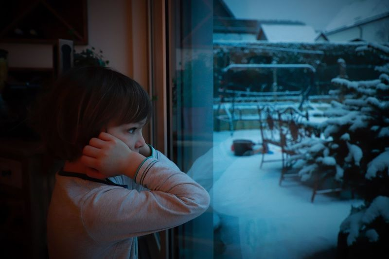 Side view of bored boy looking through window at home during winter