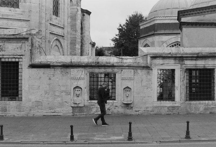 Side view of man walking on sidewalk in city