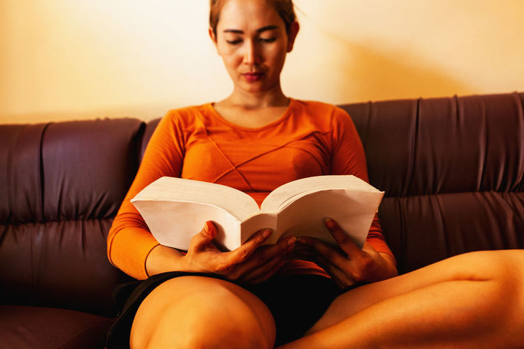 Woman reading book while sitting on sofa at home
