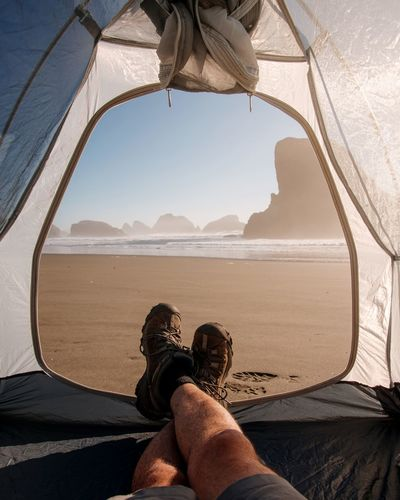 Low Section Of Man Sitting In Tent At Beach