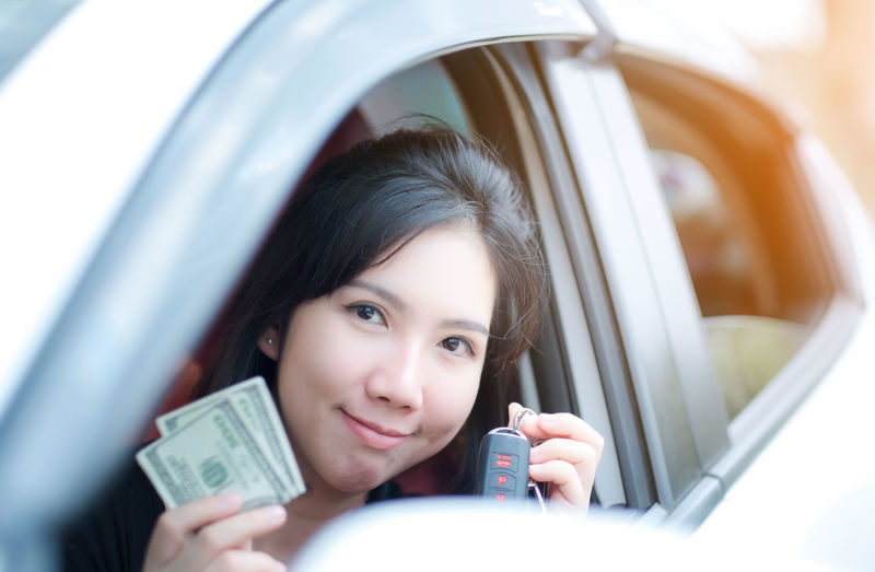 Closeup portrait happy smiling attractive asia woman sitting in her new white car showing keys, holding dollar Personal transportation purchase concept Portrait Lifestyles Headshot One Person Women Leisure Activity Mode Of Transportation Real People Car Holding Front View Young Women Motor Vehicle Young Adult Transportation Selective Focus Smiling Looking At Camera Beautiful Woman Outdoors