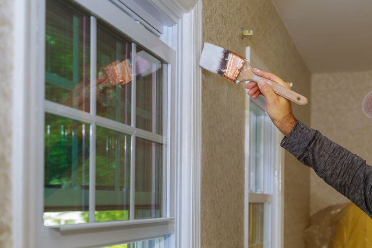 Painter painting a window trim or molding of a house Construction Home Improvement Molding Paint Renovation Worker Apartment Brush Contractor Hand Holding Human Body Part Human Hand Lifestyles Moulding One Person Paintbrush Painter Professional Real People Repairman Repairman Technician Trim Window Window Painting