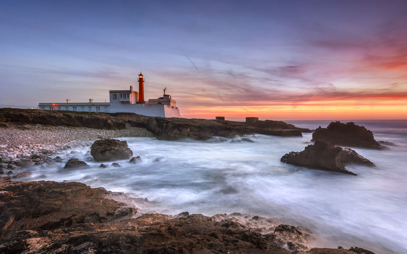 Lighthouse indicating the way to the Atlantic Ocean Lighthouse Portugal Beach Beauty In Nature Built Structure Cloud - Sky Guidance Horizon Over Water Land Lighthouse Motion Nature No People Outdoors Power In Nature Rock Rock - Object Scenics - Nature Sea Sky Solid Sport Sunset Water Wave