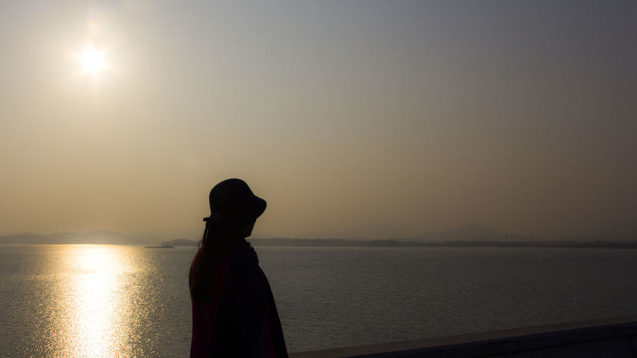 Silhouette woman standing on promenade by sea against clear sky