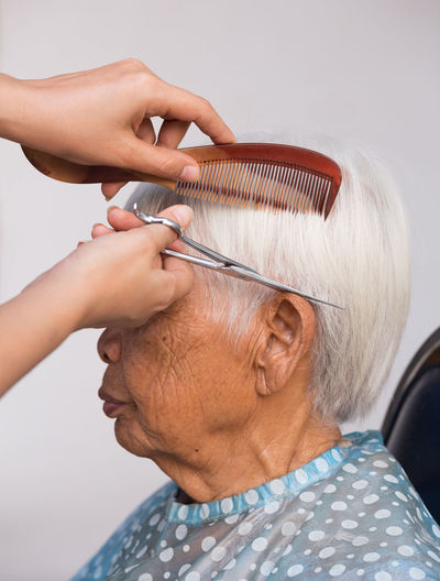 Cropped hand of barber cutting hair of senior man