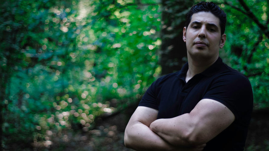 Portrait Of Muscular Man Standing Against Trees