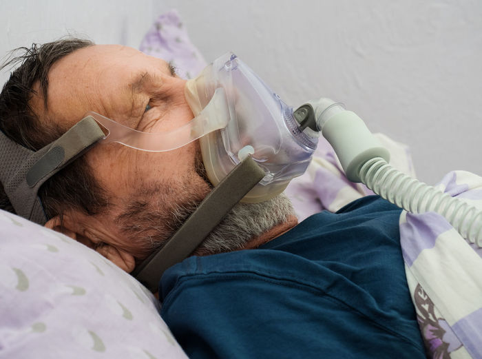 Male patient with oxygen mask lying on bed