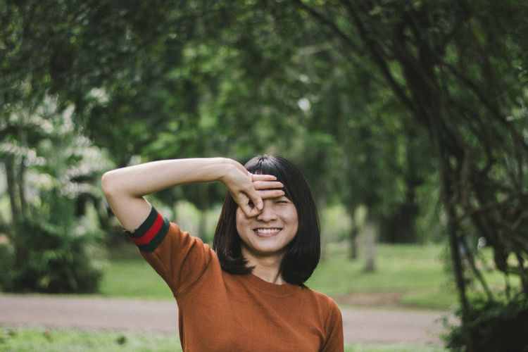Portrait of smiling young woman gesturing while standing against trees in park