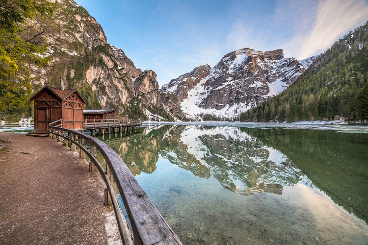 Scenic view of calm lake by mountains against sky