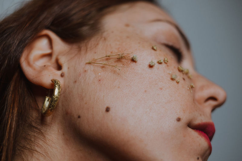 Close-Up Of Woman With Dried Flowers On Face
